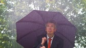 struggle : Caucasian businessman sheltering underneath an umbrella in the torrential rain