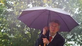 struggling : Caucasian businessman sheltering underneath an umbrella in the torrential rain