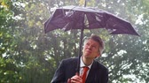 derrota : Caucasian businessman sheltering underneath a broken umbrella in the rain