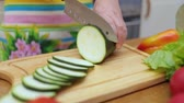 ev kadını : Womens hands Housewives cut with a knife fresh zucchini on the cutting board of the kitchen table