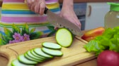 dona de casa : Womens hands Housewives cut with a knife fresh zucchini on the cutting board of the kitchen table