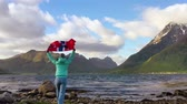 skandinávia : Woman with a waving flag of Norway on the background of nature Stock mozgókép