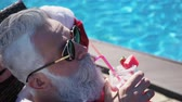 Happiness and satisfaction at the tropical new year. Crazy cheerful traveler chilling on sunbathing bad in santa costume, tanning on the sun, drinking alcohol with straw near with hotel swimming pool