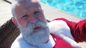 Brutal adult man in carnival red wear asks not to disturb looking at camera. Santa is annoyed and trying to having a vacation before the new year season and sunbathing in tropical resort at sunny day Dostupné videozáznamy