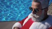 Santa on the summer recreation tanning at the smimming pool and learning how to use digital devices. Funny face portrait of old Christmas man with white beard in mirror sunglasses reflection laptop