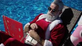 Humorous fun concept: Santa Claus are working use the laptop and hides the screen from inflatable ring, open and close computer and looking at flamingo. Summertime recreation at swimming pool area