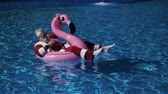 Handsome Santa floating in flamingo inflatable ring into the swimming pool with cocktail glass in hand, chilling and enjoying tropical New Year. Pleasure and happiness concept. Inspiration background