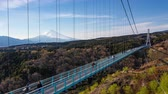 skywalk : Time lapse of people crossing Mishima Sky Walk in Mishima,  Japan with view of mount Fuji in background