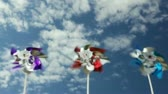 motion blur : Pinwheels spinning in breeze against blue sky and clouds