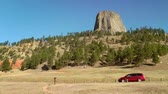 weg : Auto rijden langs de Devils Tower National Monument, Wyoming Stockvideo