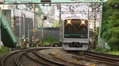 pendulares : Commuter train passing by, train tracks, Tokyo, Japan