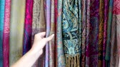 marroquino : Woman Shopping Inspecting Textiles Central Square Market Stalls Marrakesh Morocco Stock Footage