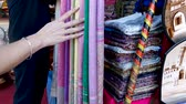 marroquino : Girl Shopping Inspecting Textiles Central Square Market Stalls Marrakesh Morocco Stock Footage