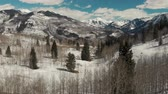 Aspen, United States - April 19, 2019: Drone shot of scenic landscape of the rocky mountains, forests and snowy back roads near Aspen Colorado Stok Video