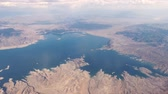 air quality : Mid Flight, United States - April 19, 2019: View of flying above white clouds with mountains and lake mead below on commercial flight to Las Vegas USA.