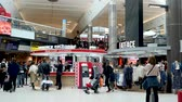 коммерческий : London, United Kingdom - April 19, 2019: Families, Passengers and shoppers walking through London Gatwick Terminal, Shops and Restaurants in departure lounge