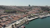 поднятый : Porto, Portugal - September 1, 2019: 4k Drone 360 degree PAN Aerial view of Porto Bairro da Ribeira riverside waterfront property and boats. Views of the iconic Luís I Bridge, River Douro and Gaia