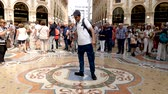 hurafe : Milan, Italy - June 30, 2019: 4k Male Tourist spinning on the bulls balls mosaic in Milan tradition at the Galleria Vittorio Emanuele II a glass-covered 19th-century arcade off the Piazza del Duomo