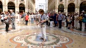 milano : Milan, Italy - June 30, 2019: 4k Woman Tourist spinning on the bulls balls mosaic in Milan tradition at the Galleria Vittorio Emanuele II a glass-covered 19th-century arcade off the Piazza del Duomo Stock Footage