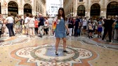 hurafe : Milan, Italy - June 30, 2019: 4k Beautiful Young Girl Lady Woman Tourist spinning on the bulls balls mosaic in Milan tradition at the Galleria Vittorio Emanuele II arcade off the Piazza del Duomo