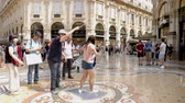 суеверие : Milan, Italy - June 30, 2019: 4k Asian Lady Woman Tourist spinning on the bulls balls mosaic in Milan tradition at the Galleria Vittorio Emanuele II arcade off the Piazza del Duomo