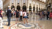 hurafe : Milan, Italy - June 30, 2019: 4k Asian Lady Woman Tourist spinning on the bulls balls mosaic in Milan tradition at the Galleria Vittorio Emanuele II arcade off the Piazza del Duomo
