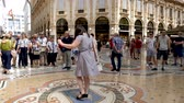 hurafe : Milan, Italy - June 30, 2019: 4k Woman Tourist spinning on the bulls balls mosaic in Milan tradition at the Galleria Vittorio Emanuele II a glass-covered 19th-century arcade off the Piazza del Duomo Stok Video