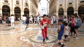 hurafe : Milan, Italy - June 30, 2019: 4k Asian family tourists spinning on the bulls balls mosaic in Milan good luck tradition at the Galleria Vittorio Emanuele II arcade off the Piazza del Duomo Stok Video