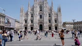 Milan, Italy - June 30, 2019: 4k Slow Motion shot of Tourists visiting the Piazza del Duomo to see top tourist attractions the Duomo del Milano and shopping at Galleria Vittorio Emanuele II Milano