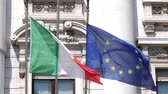 Milan, Italy - June 30, 2019: 4k Italy Italian & EU European Union Flag flying together in front of the Bank of Italy. Finance, money and commerce of Palazzo della Banca Commerciale Italiana Wideo