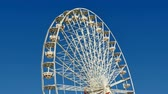 fairgrounds : Tall Classical Fair Ferris Wheel In France.  Ferris wheel on the banks of the Garonne River in Toulouse, France. Fair Ferris Wheel spinning at sunset. Fairground in France. Amusement park for children. Big recreation funfair for kids leisure time.