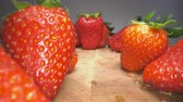 Dolly shot of red juicy strawberries on wooden background. Sweet harvested strawberry background, healthy food lifestyle