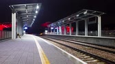Modern railway train station at night. Bright colors and blurred rapid movement. Dostupné videozáznamy