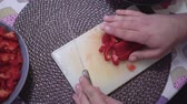 Caucasian man slicing red pepper or paprika into small dice or cubes.