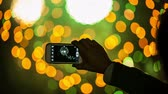 quarto : woman filming colorful fireworks on her smartphone