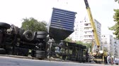 Болгария : A crane machine is drawing the cargo tank of an overturned truck near the main street of a small town.