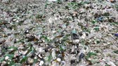 Glass waste for recycling in a recycling facility. Different glass packaging bottle waste. Glass waste management. Process of waste glass into usable products. Pile of different bottles. Zooming out.