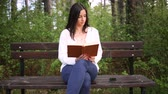 Attractive young woman dressed casually reads old book sitting on a wooden bench in the forest. Phone rings and she picks up and talks on the phone. Smiling while reading. Slide (slider) shot. Vídeos