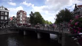 j��zda na kole : AMSTERDAM - AUGUST 29: Cyclists ride on the bridge in old town on August 29, 2014 in Amsterdam.