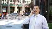 manmetro : Middle age businessman speaking using smartphone in modern downtown Stock Footage