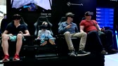 head mounted display : Moscow, Russia - June 11, 2017: People with an immersive VR content viewing experience at Samsung Gear VR Theater with 4D Chair in modern Interactive space Galaxy S8 Studio in Megapolis Shopping Mall.