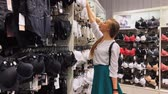 выборе : Moscow, Russia - Mart 16, 2018: Young slim woman chooses a bra in an underwear store at mall Стоковые видеозаписи