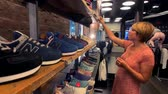 выборе : New York, USA - September 6, 2018: Woman choosing New Balance sneakers in the company store on 5th Avenue
