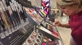 escolher : New York, USA - September 6, 2018: Woman testing makeup in Macys store Vídeos