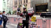 demonstrace : New York, USA - September 6, 2018: Man selling anti-Trump badges and souvenirs on the background of Trump tower