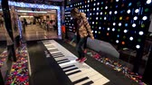 fortepian : New York, USA - September 6, 2018: Buyers having fun with big floor piano in Macys store at Manhattan Wideo