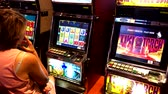 elbise : Las Vegas, USA - September 10, 2018: Woman playing slot machine in casino
