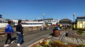 éttermek : San Francisco, USA - September 10, 2018: Tourists visit famous landmark Pier 39 at sunny day time Stock mozgókép