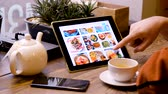 işadamı : Moscow - February 15, 2019: Man looks at pictures of healthy eating on the Internet using tablet pc Stok Video