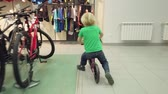 選択 : Pyatigorsk, Russia - April 19, 2019: Boy testing and riding bicycle in the sport shop 動画素材